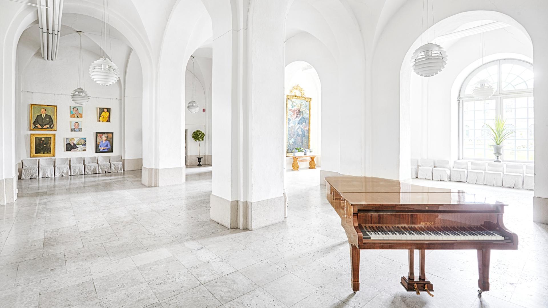 Vy över Stensalen. En vit och ljus sal med en flygel i förgrunden.