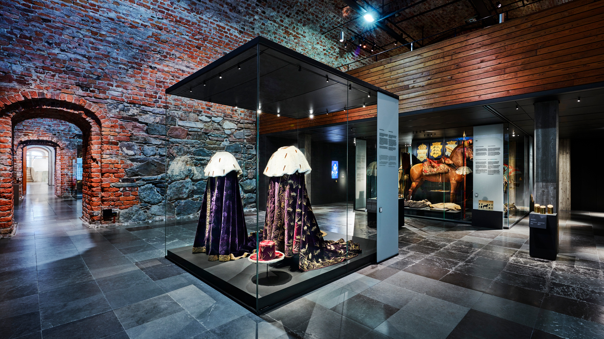 A museum case in The Royal Armoury with two royal velvet mantles.