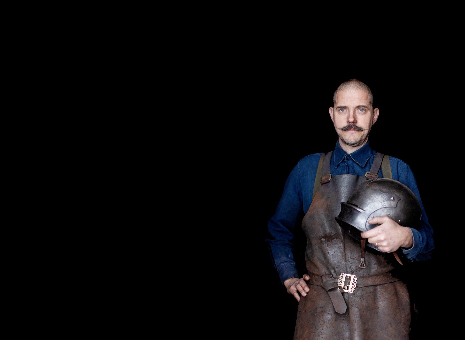 Rustningsmakaren Albert Collins som står och håller i en hjälm tillhörande en rustning