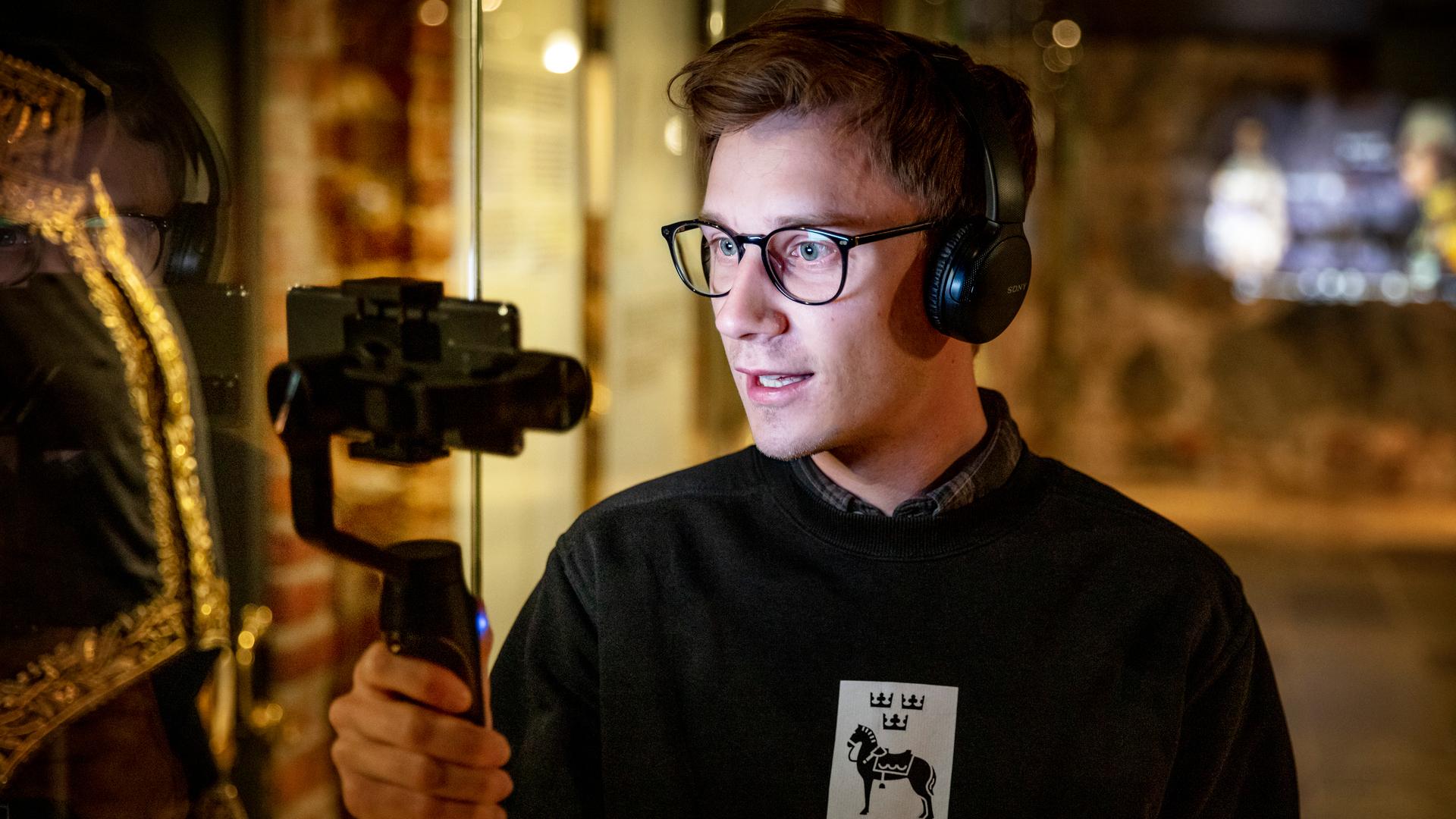 Skolpedagog som håller i en digital visning genom att hålla i en handkamera och visa runt i museet.