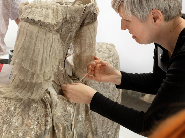 En textilkonservator som syr i Drottning Sofia Magdalenas bröllopsklänning