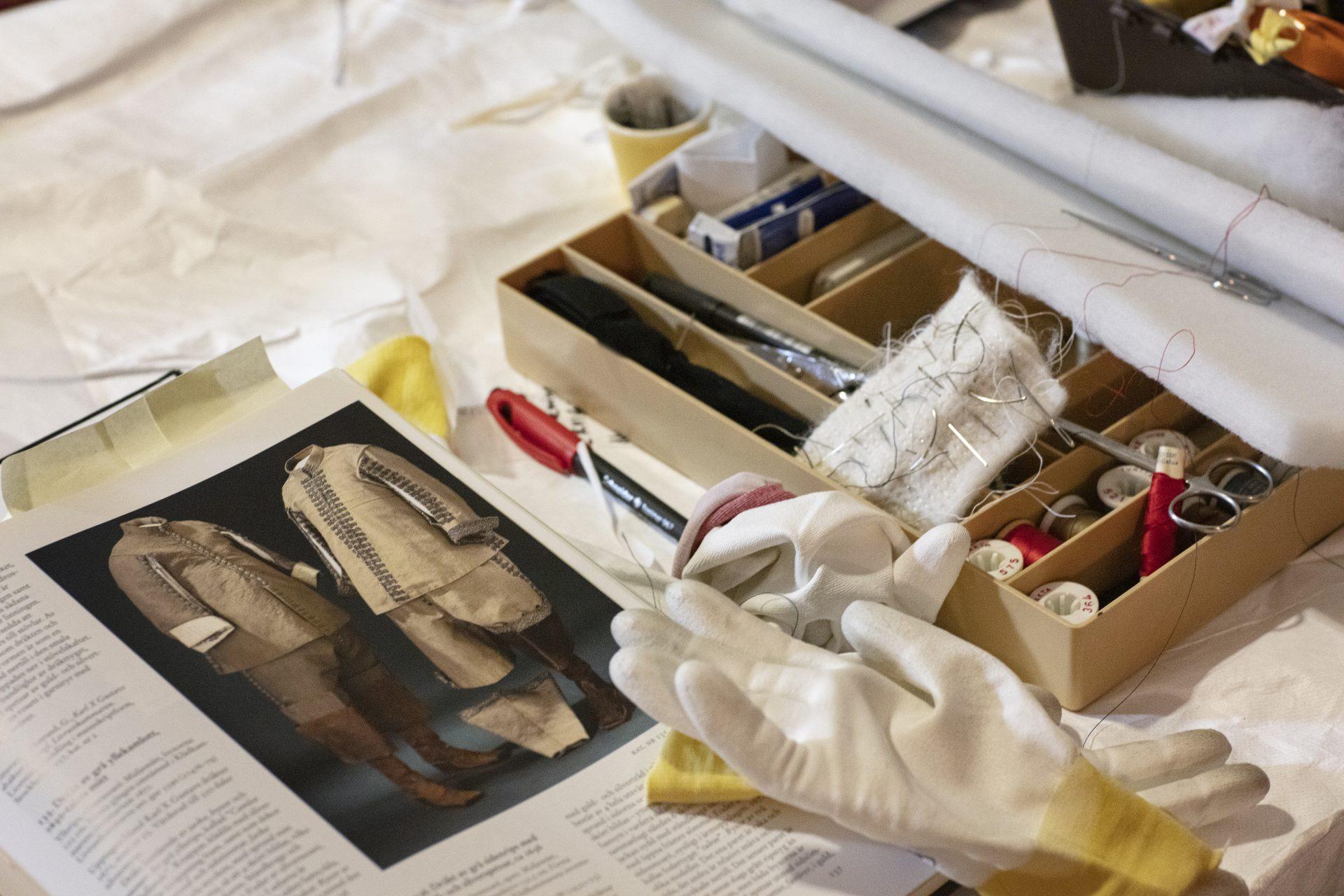 Konservatorns skrivbord, en sylåda och vita handskar bland annat.