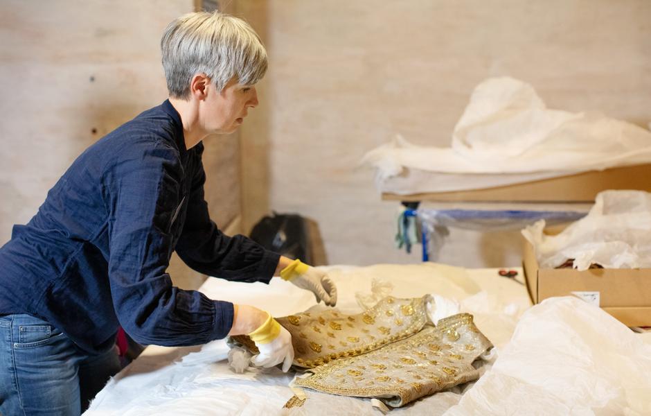 Textilkonservator Augusta Persson tar hand om västen till Karl XIII:s kröningsdräkt
