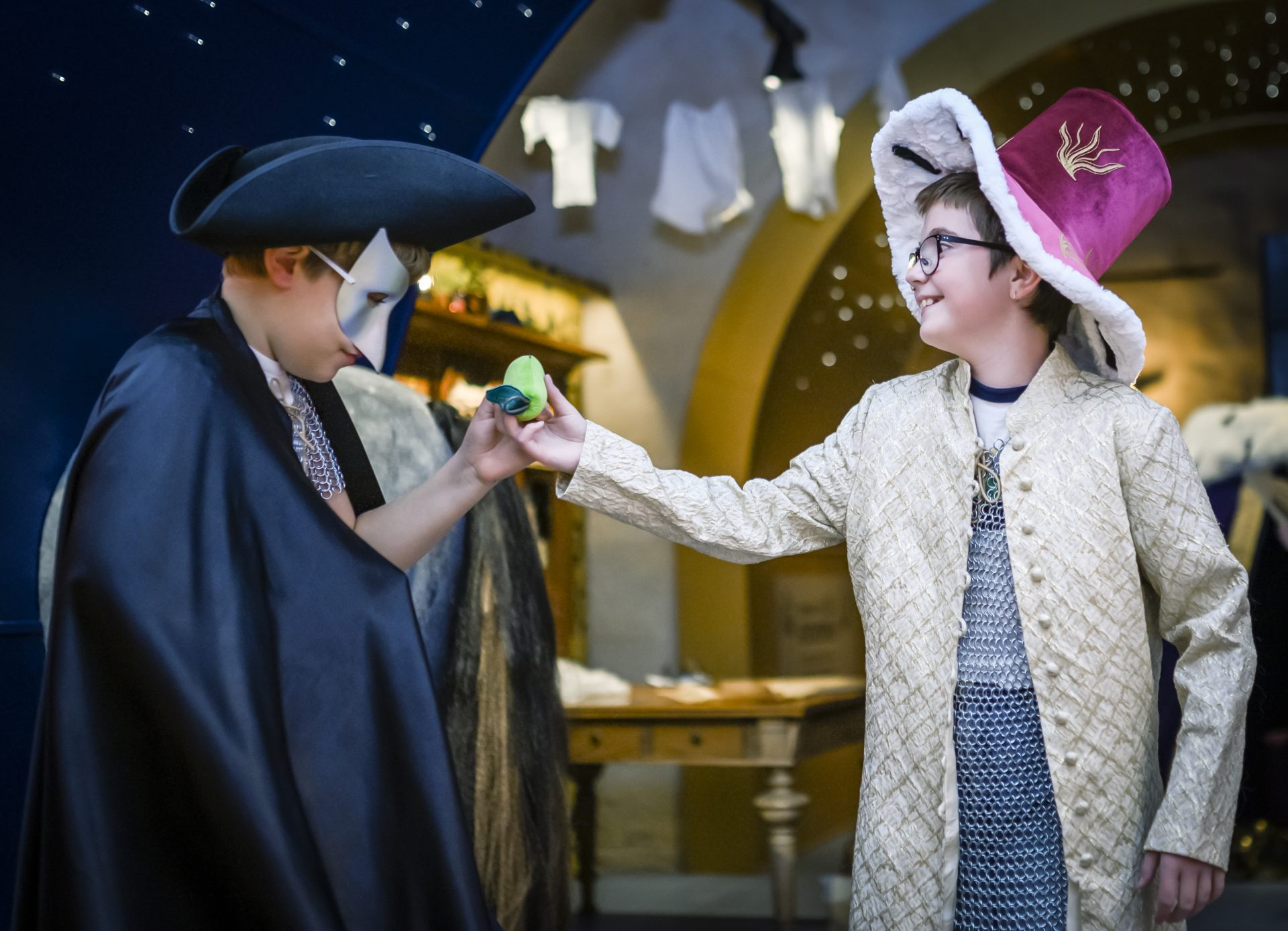 Två barn som är utklädda i kungliga kläder och leker i Lilla Rustkammaren