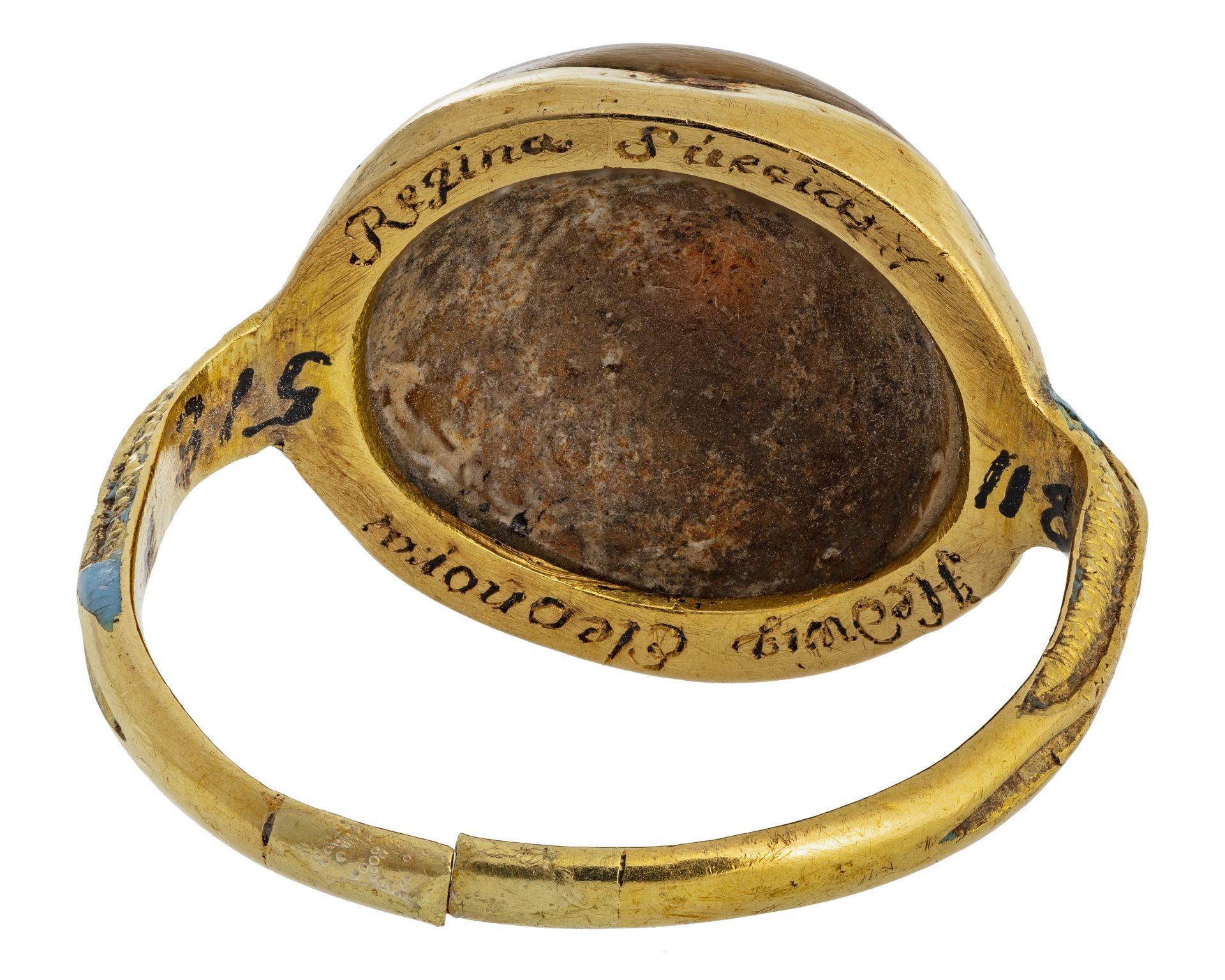 Baksidan av en guldring med inskriptioner.