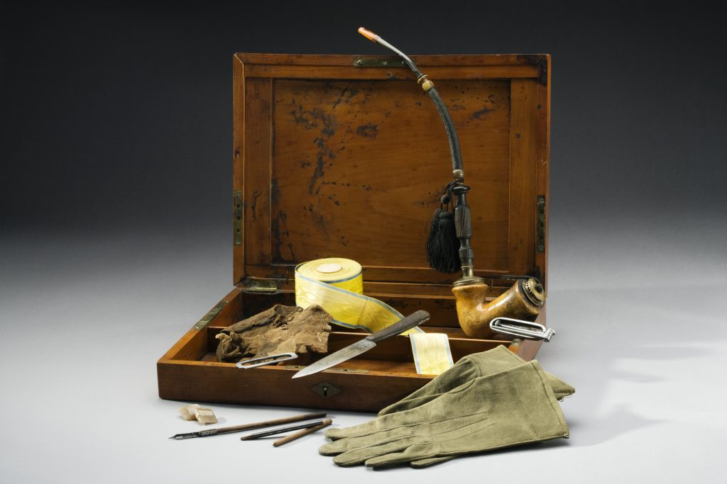 A wooden box with a number of artifacts.