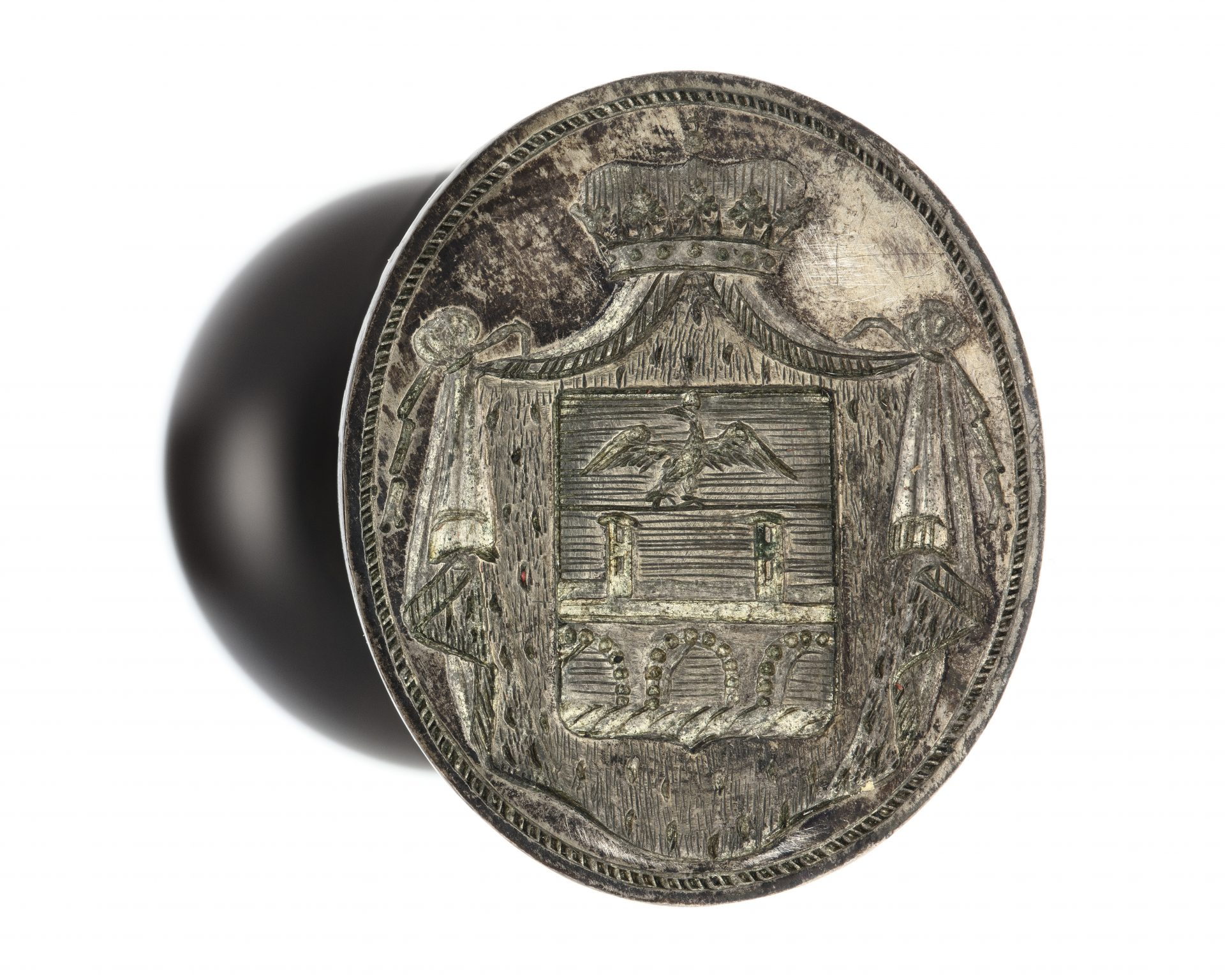 A seal of steel with an engraved coat of arms.