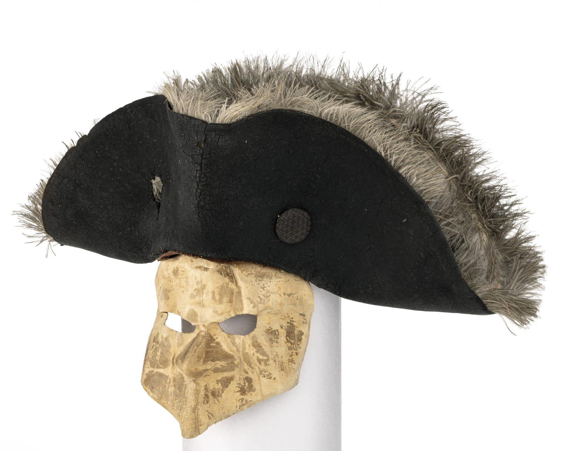 En vit mask och en svart hatt.