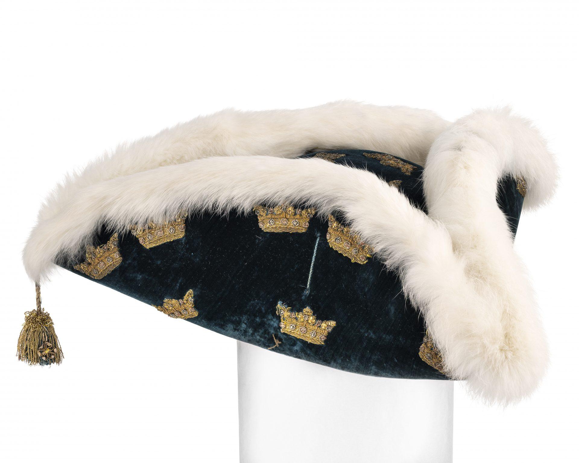 En blå, trekantig hatt med påsydda guldkronor och strutsfjädrar runt brämen.