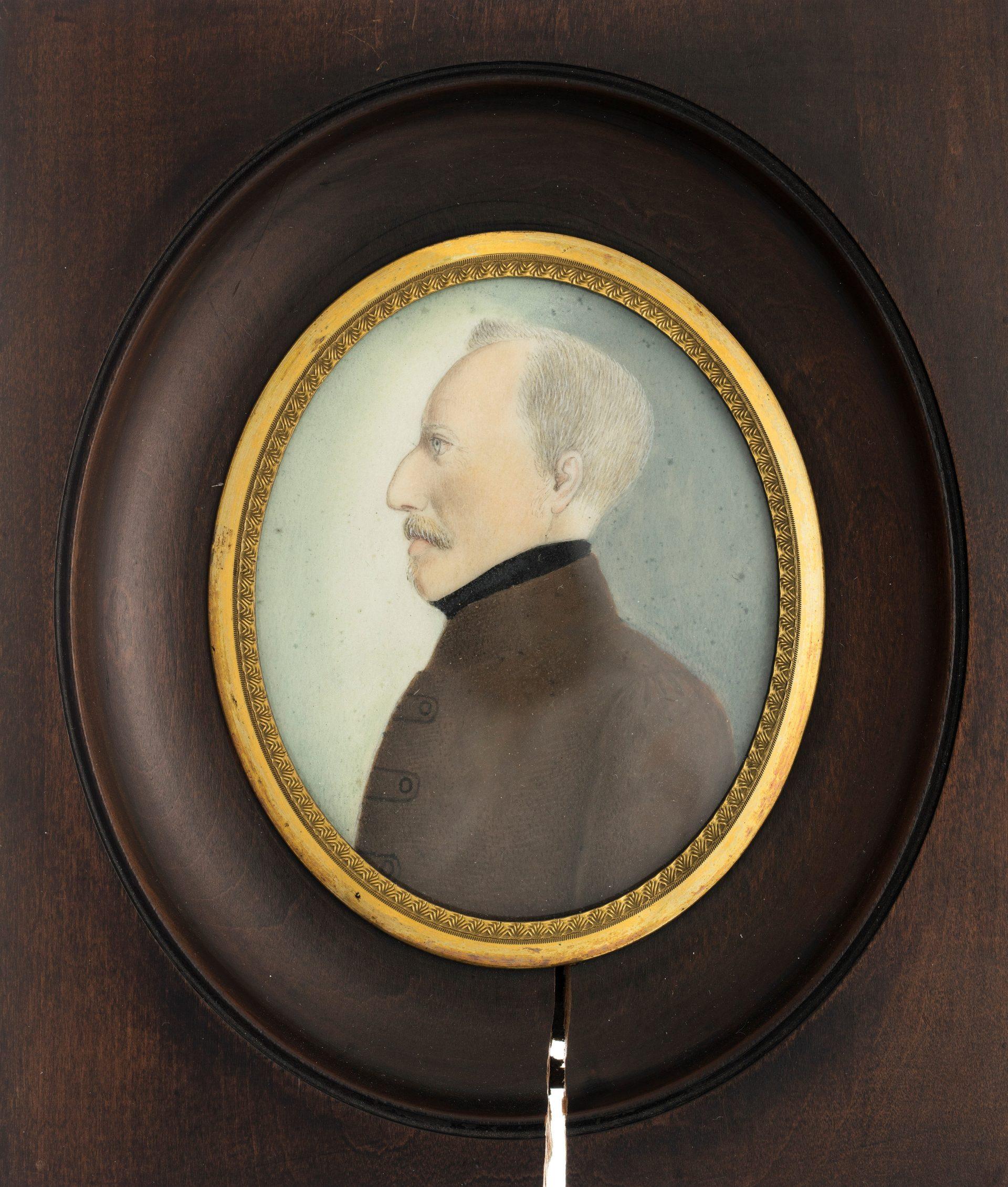 Ett porträtt av en medelålders man i profil i en brun ram.
