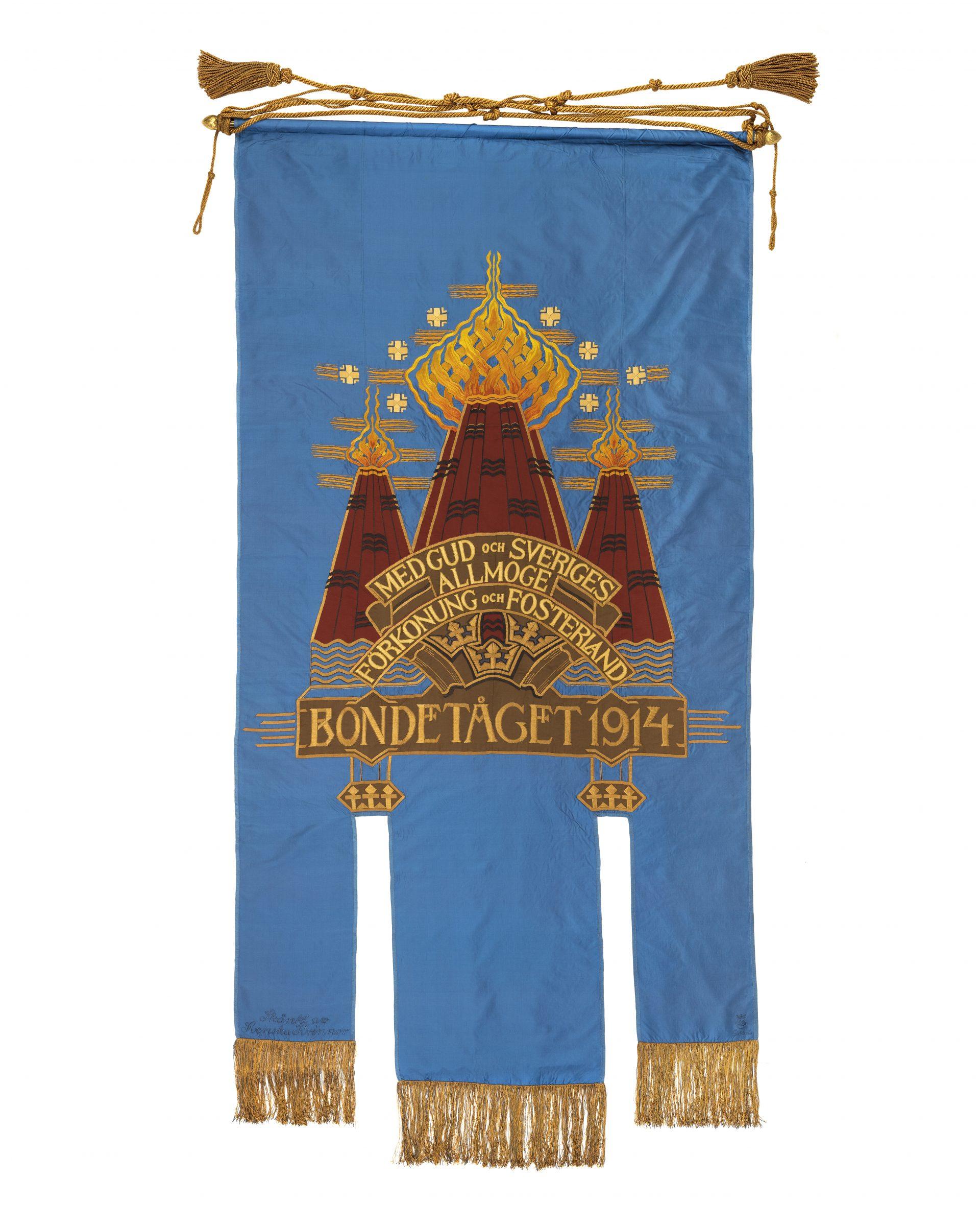 En blå fana med Bondetåget 1914 broderat i mitten.