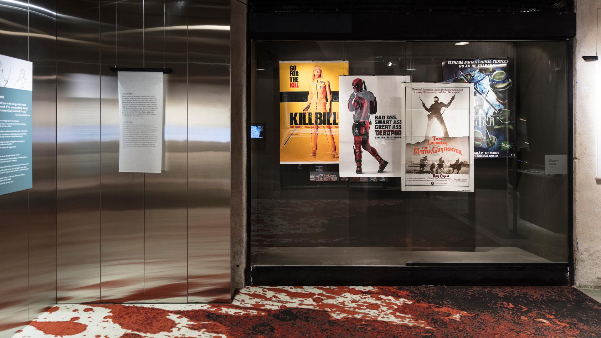I utställningslokalen var ett golv fyllt med låtsas blod och i en monter syns fyra filmaaffischer, bland annat Kill Bill