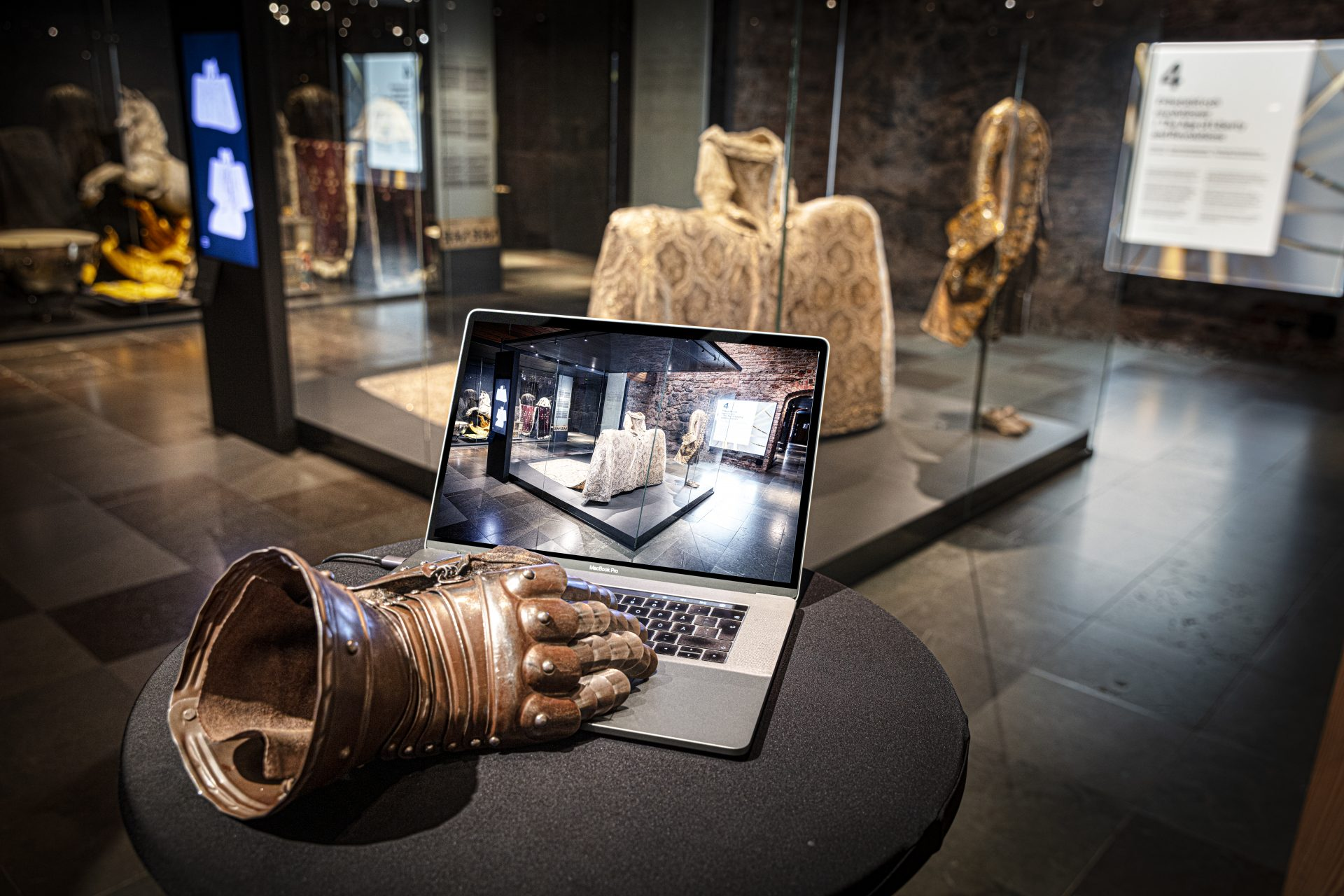 En riddarhandske knappar på en laptop inne i utställningen om Sveriges kungliga historia.