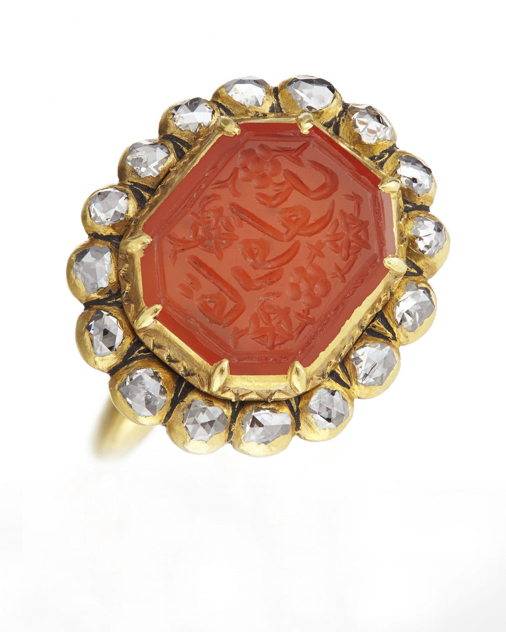Guldring med ädelsten runt om och en större röd sten med inskription på arabiska.