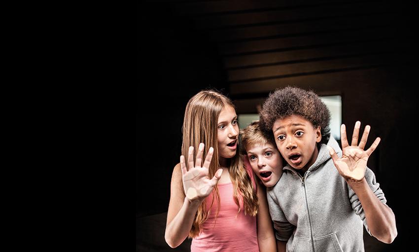Tre ungdomar med händerna på en glasskiva ser förvånade ut.