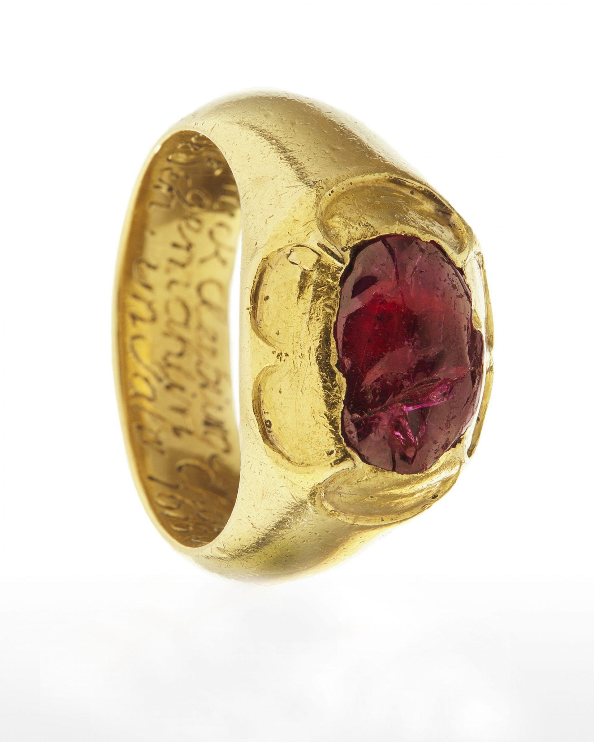 Guldfärgad ring med röd sten.