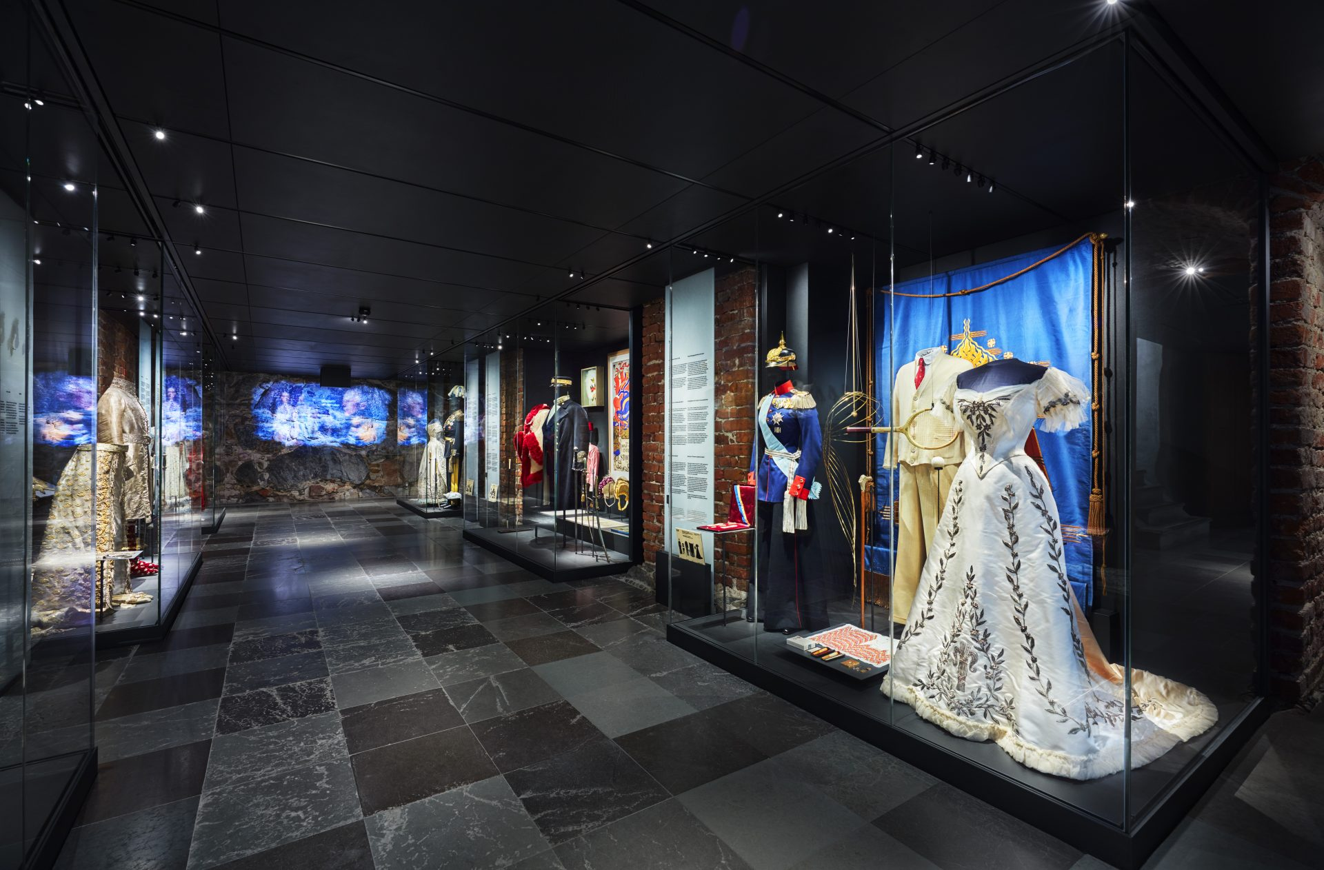 A view of a display case with a gown and a uniform.