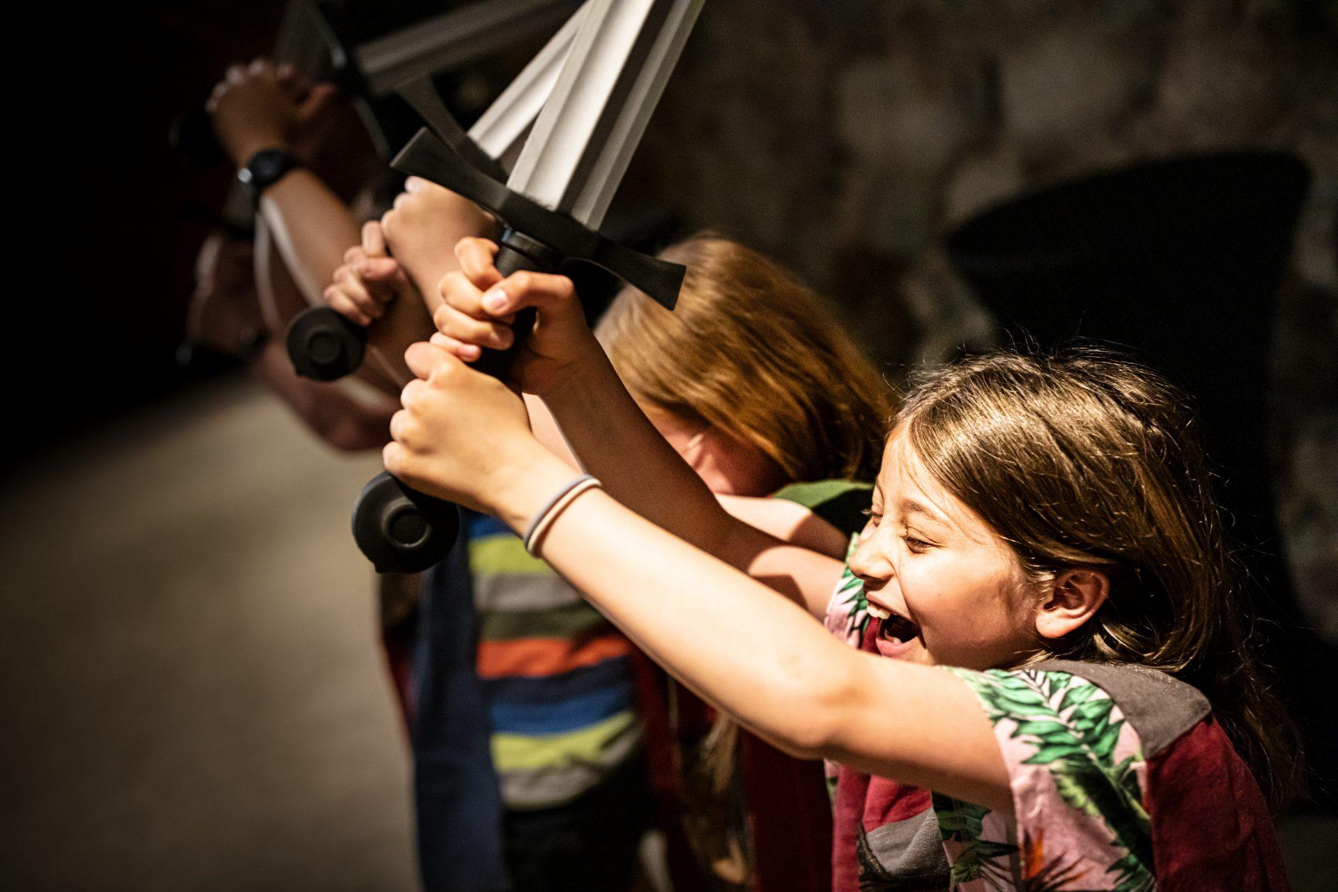 Barn som står på rad och håller i varsitt svärd