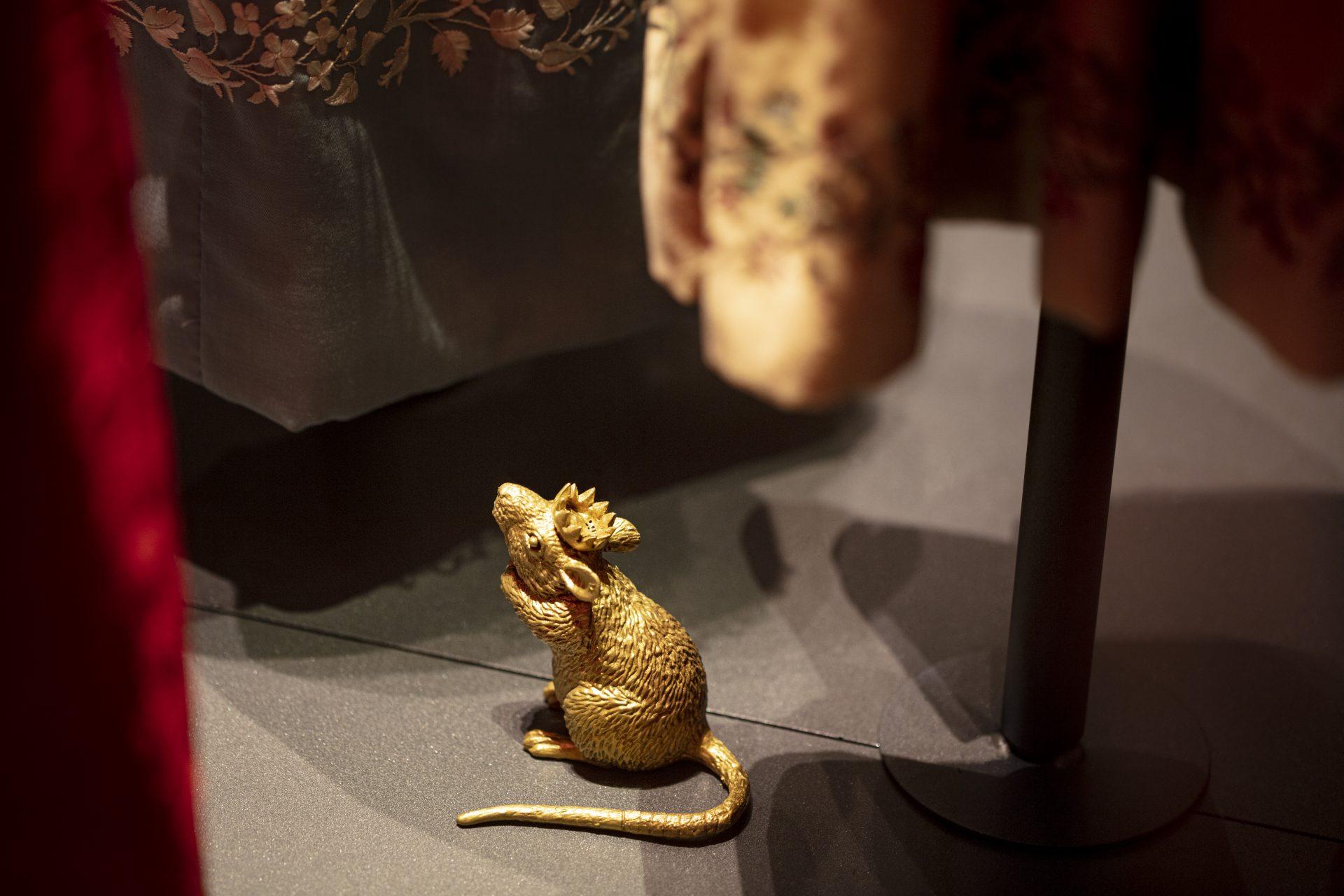 En liten guldig mus med kungakrona som sitter och tittar upp mot en kunglig klänning.