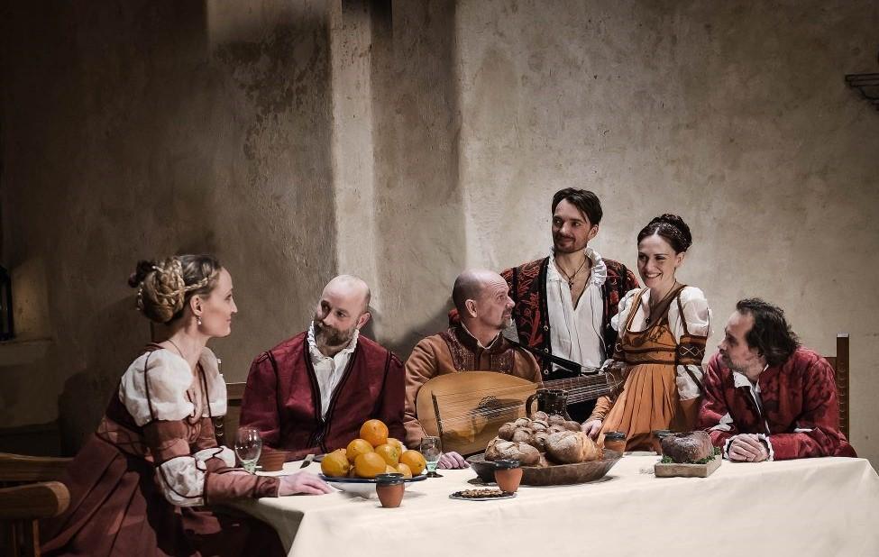 Romeo och Julia kören sitter vid ett dukat matbord och är uppklädda i renässanskläder