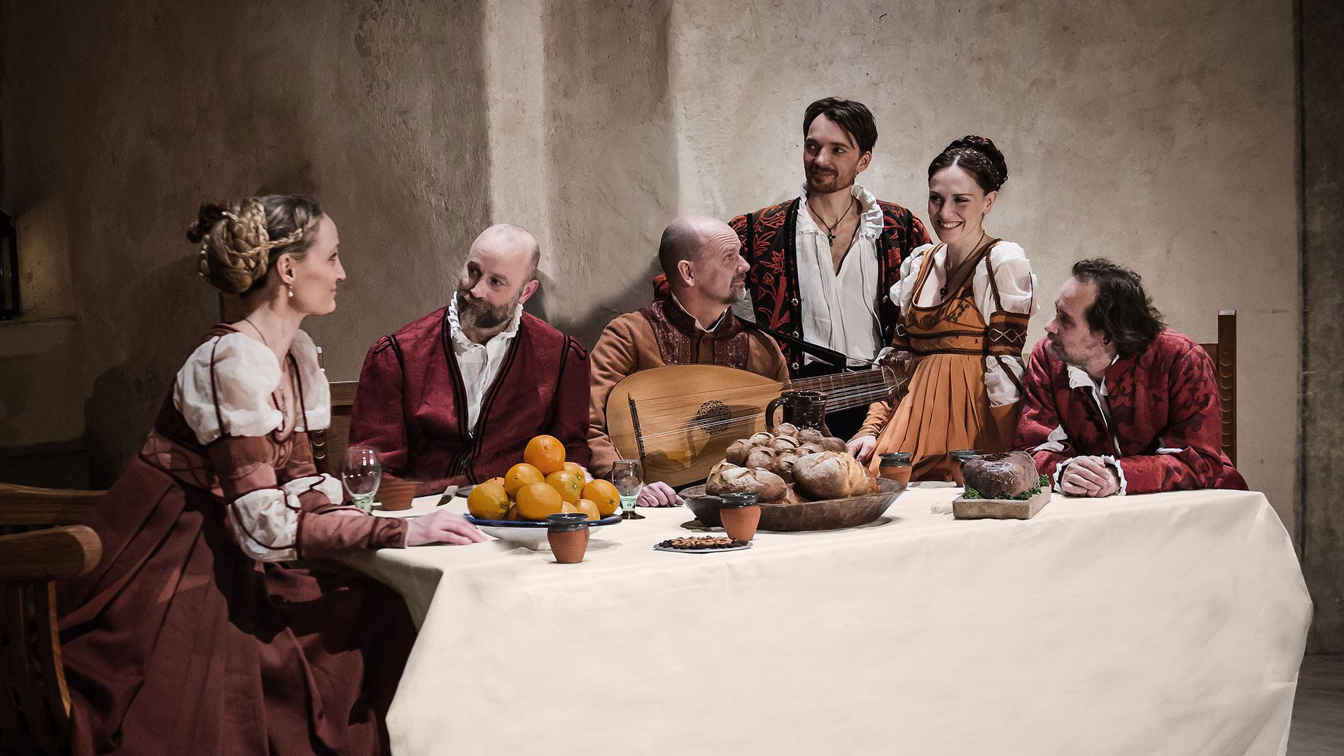 Romeo och Julia kören sitter vid ett uppdukat matbord iklädda renässanskläder.